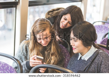 Three women looking a smart phone on the bus. They are a mixed group with a caucasian, an asian and a spanish woman. They are friends and they are travelling together by bus. - stock photo