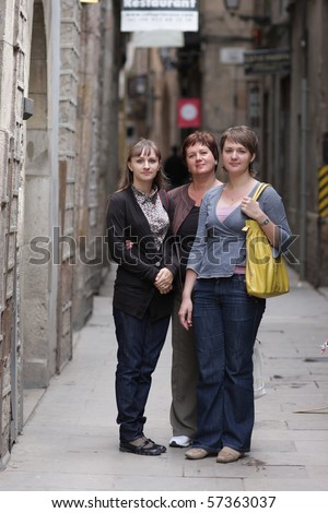 Three women poses at the street of gothic quarter of Barcelona - stock photo