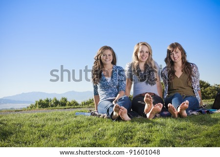 Three women relaxing in the outdoors - stock photo