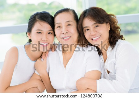 Three women sitting and embracing