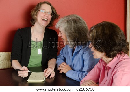 Three women sitting at a table sharing a hearty laugh - stock photo