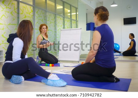 Three women (teacher and two students) are in fitness hall during personal training, focus on teacher