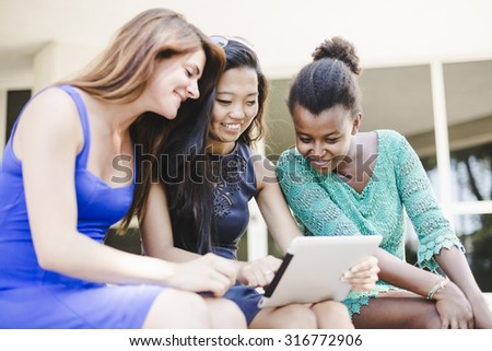 Three women using technology at the park