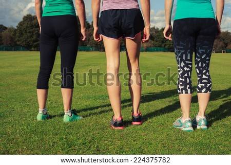 Three women wearing sportswear are standing in the park on a sunny day - stock photo