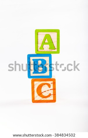 Three wooden alphabet blocks stacked up with the letter a on top followed by b and then c
