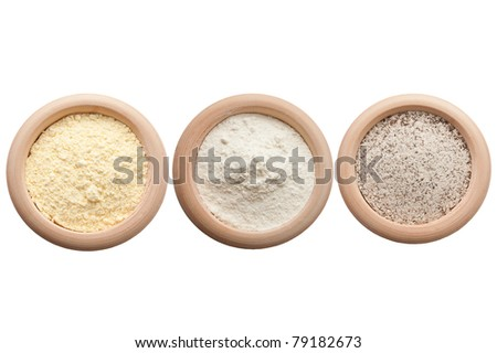 Three wooden bowls with corn, white and buckwheat flour - stock photo