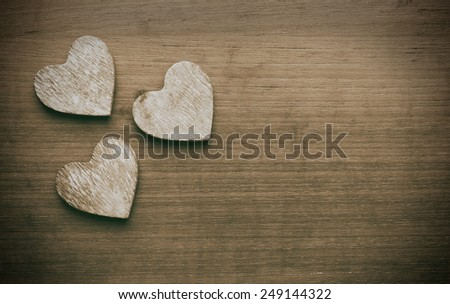 Three wooden hearts on a grungy wooden background - stock photo