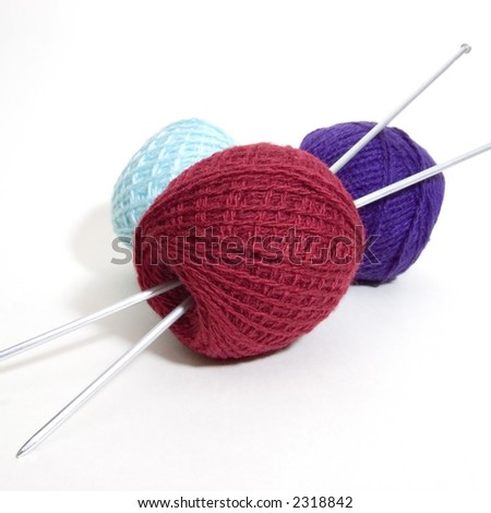 Three wool balls and knitting needles. Needles go through the wool ball (isolated on white)