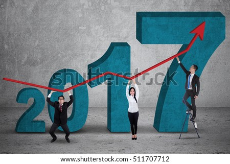 Three workers holding growth graph while standing in front of numbers 2017 while working together