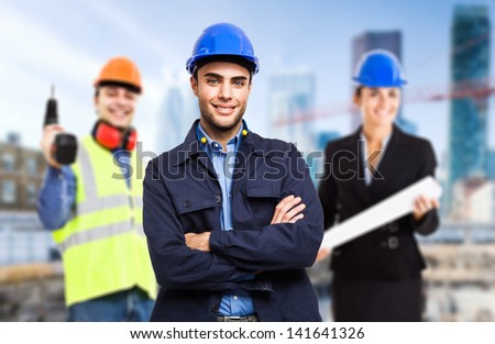 Three workers in front of a construction site - stock photo