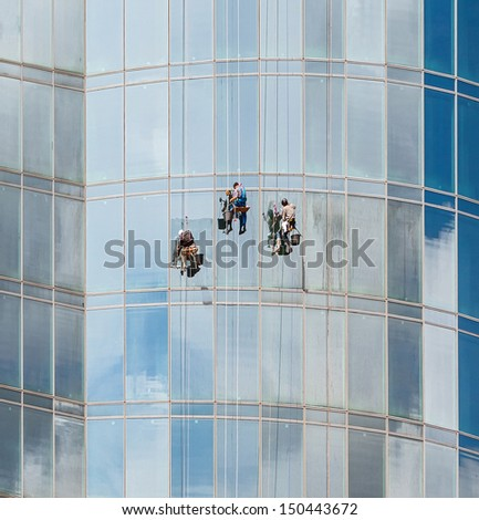 Three workers wash the glass in a modern office building, using the technique of climbing - Moscow, Russia