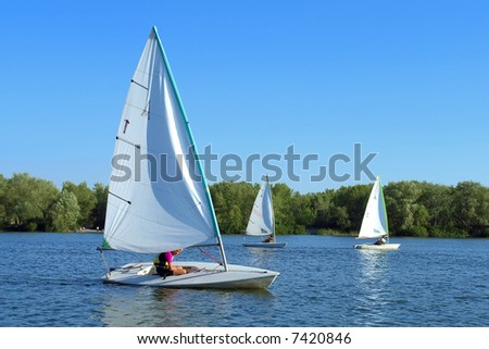 Three yachts cruise on river. Shot in July, Dnieper river, Ukraine.