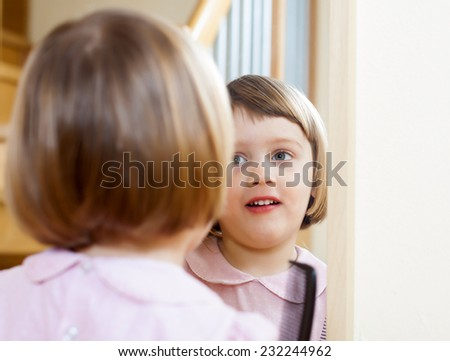 three year old child brushing her hair front of  mirror - stock photo