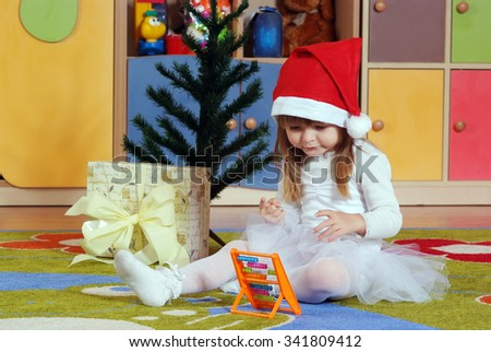 Three year old girl dressed as an angel playing in the nursery