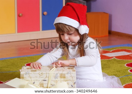 Three year-old girl dressed in a Santa Claus hat gets a a present - stock photo