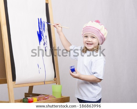 Three-year-old girl playing in the artist. Girl draws on the easel paints