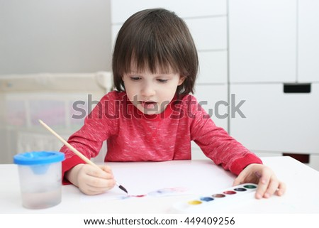 Three-years boy is painting with watercolor