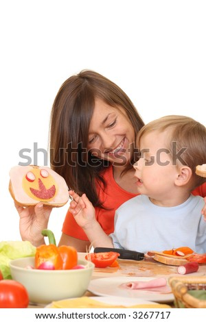 three years old boy having breakfast with mother isolated on white