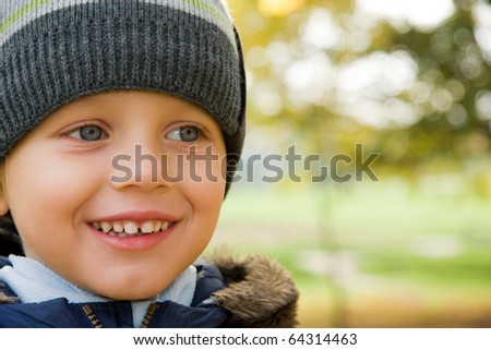 Three years old boy in cap smiling in autumn scenery - stock photo