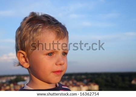Three years old boy over blue sky. Small town in a background - stock photo
