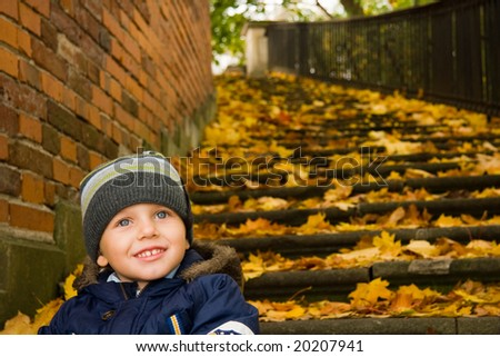 Three years old boy smiling in autumn scenery - stock photo