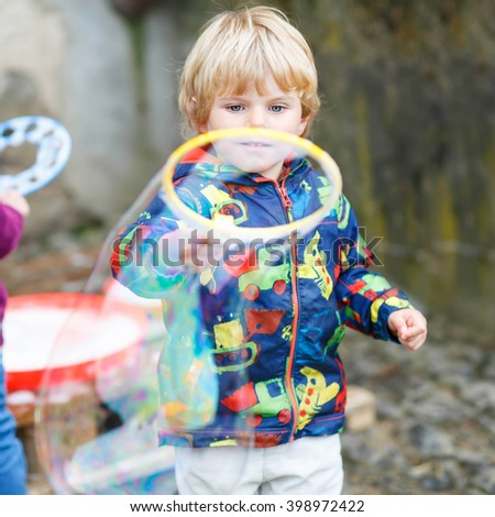 Three years old caucasian child boy blowing soap bubbles outdoor on birthday party - happy carefree childhood. Kid having fun. - stock photo