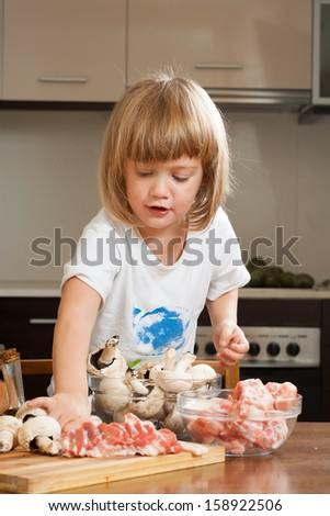 Three years-old child cooking in kitchen - stock photo