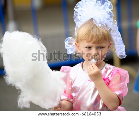 Three years old  girl with white cotton candy. - stock photo