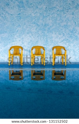 three yellow chairs at the swimming pool - stock photo