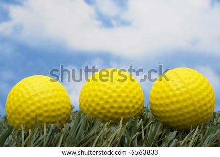 Three yellow golf balls sitting on grass - stock photo
