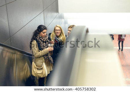 Three young adult women dressed in coat and scarves moving up on escalator in building with copy space on side