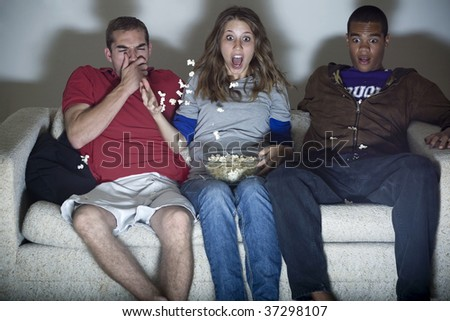 Three young adults are horrified at what they're watching. - stock photo