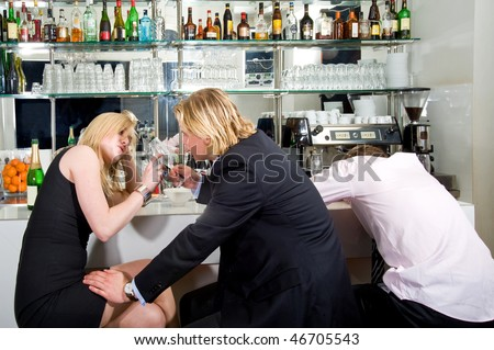 three young adults sitting at a bar; one sleeping, the others flirting with each other - stock photo