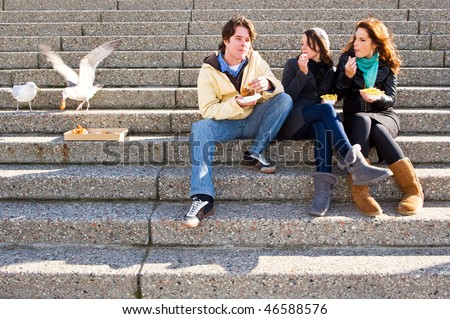 Three young adults sitting on concrete stairs, eating fish and chips, whilst two seagulls steal a bit of cod cheeks, - stock photo
