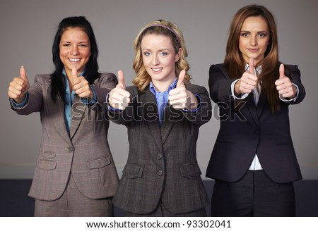 Three young and attractive businesswoman show thumbs up gesture - stock photo