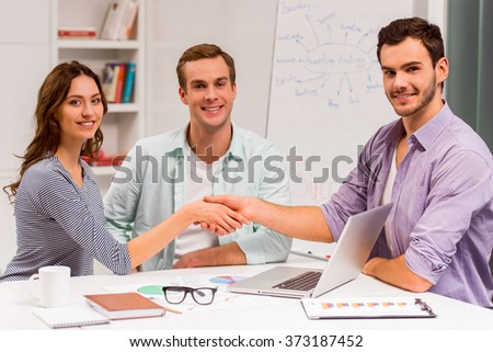 Three young attractive businesspeople in casual clothes smiling and looking in camera while working in office. Man and woman shaking their hands.