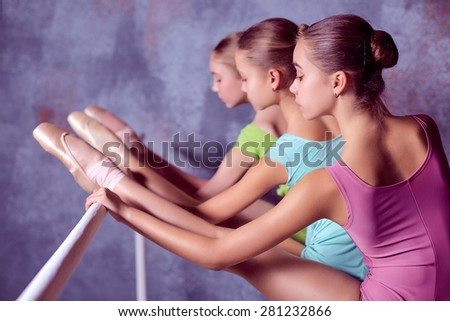 Three young ballerinas stretching on the bar on lilac background - stock photo