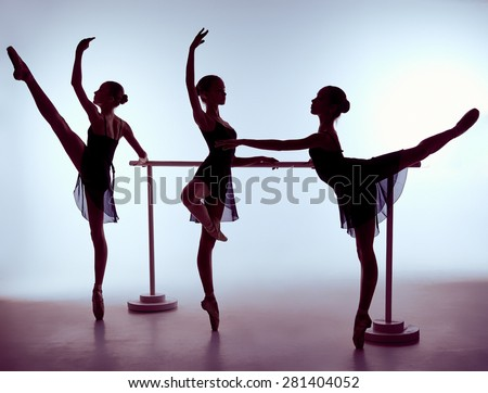 Three young ballerinas stretching on the bar on lilac background. The outline shooting - silhouettes of girls. - stock photo
