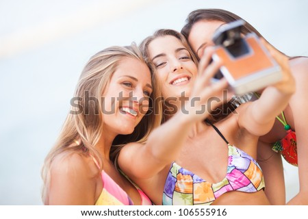 three young beautiful girlfriends having fun on the beach with a vintage camera - stock photo