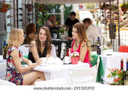Three young beautiful girls girlfriend drinking tea in a summer cafe - stock photo