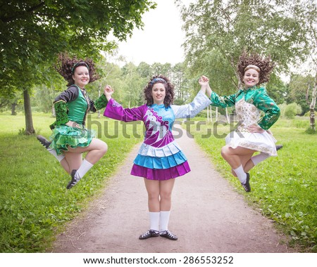 Three young beautiful girls in irish dance dress and wig posing outdoor - stock photo