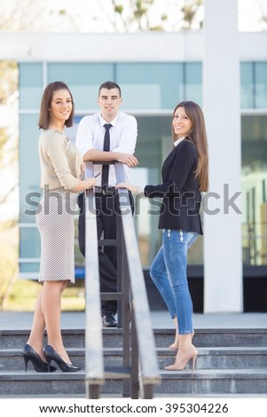 Three young business people on a coffee break in front of the office building. Portrait of young man standing on top of the stairs with two women looking at camera over their shoulders. - stock photo
