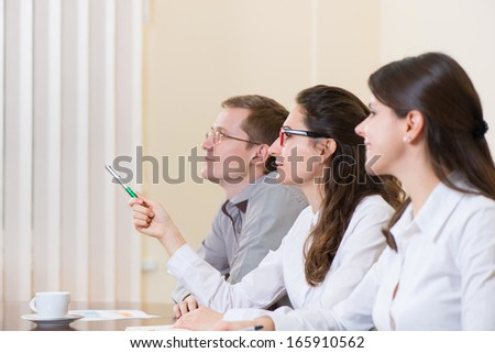Three young business people sitting at seminar - stock photo