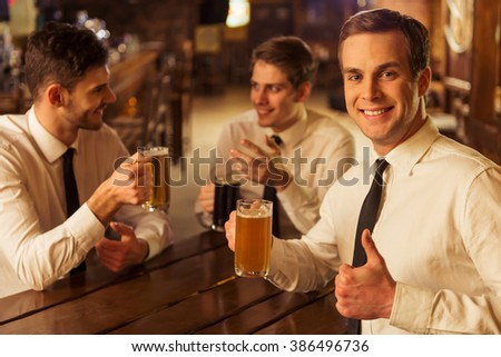 Three young businessmen in white classic shirts are talking, smiling and drinking beer while sitting in pub, blond man is showing Ok sign - stock photo