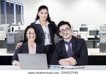 Three young businesspeople looking and smiling on the camera with laptop computer on the table, shot in the office - stock photo