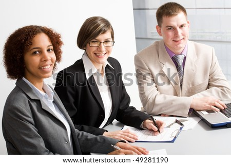 Three young businesspeople looking at camera - stock photo