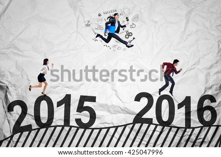 Three young businesspeople racing to get success by jumping and running above numbers 2015 to 2016 - stock photo