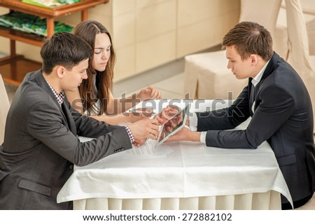 Three young businesspeople sitting in a meeting at the table and working on the tablet. Top view of the three confident and successful businessmen. - stock photo