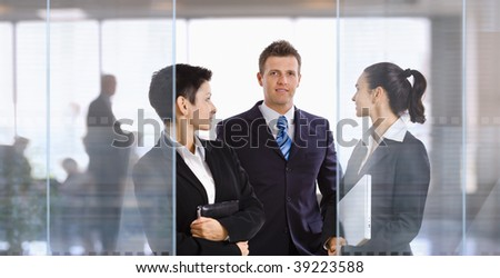 Three young businesspeople standing in modern office talking and smiling. - stock photo