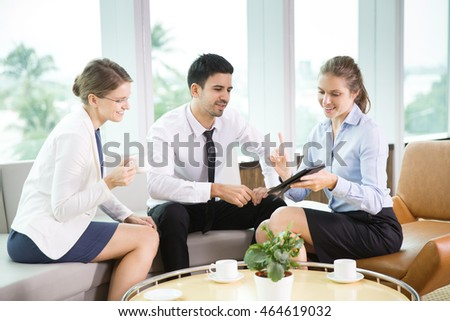 Three Young Caucasian Business People Using Tablet PC in Cafe